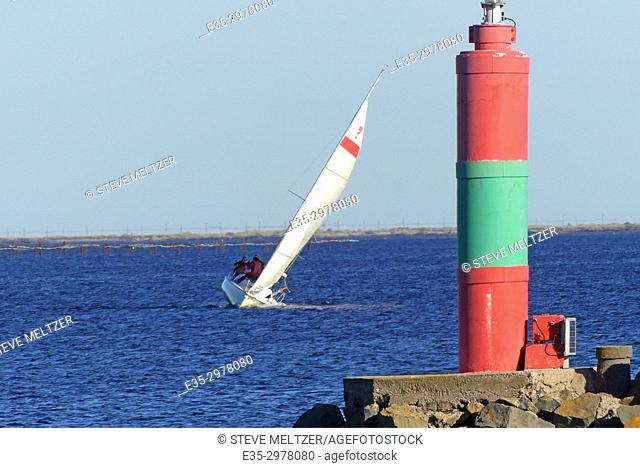 A sailboat tacks in the wind to make headway toward the port