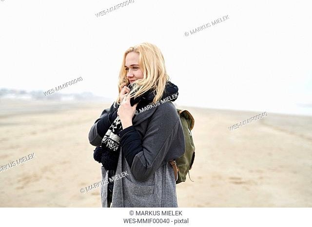 Portrait of blond young woman with backpack on the beach in winter