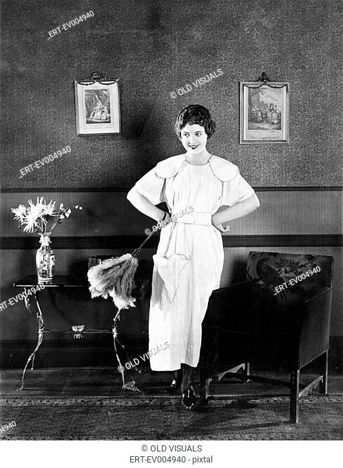 Young woman in an apron and a duster standing in a living room All persons depicted are not longer living and no estate exists Supplier warranties that there...