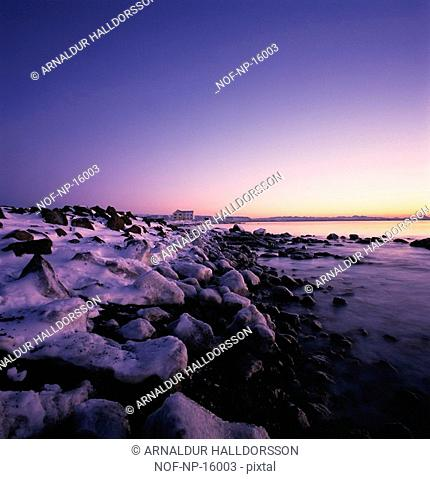 Snow and rocks by the sea
