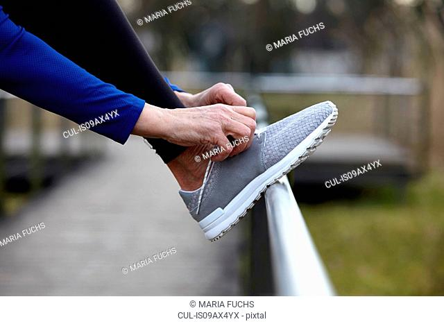Cropped side view of woman leg raised on railings tying shoelace