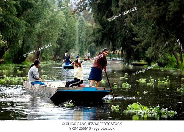 Residents ride in a boat through the water canals of Xochimilco on the south side of Mexico City. The water canals and gardens in Xochimilco was once part of...