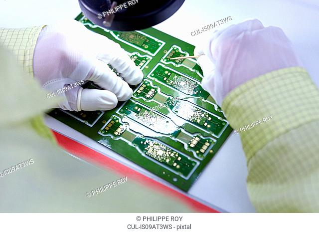 Young woman working at factory producing flexible electronic circuit boards. Plant is located in the south of China, in Zhuhai, Guangdong province