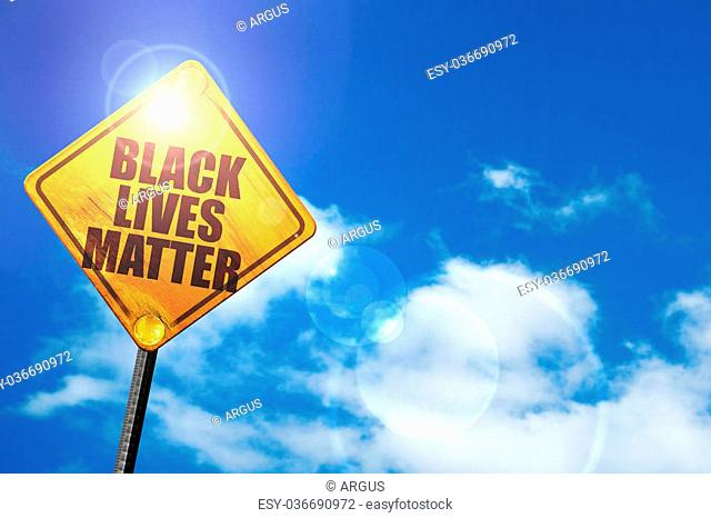 black lives matter: yellow road sign with a blue sky and white clouds