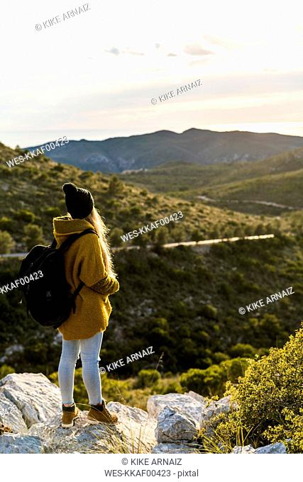 Young woman standing on rock in nature looking at view