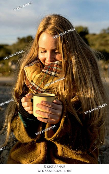 Smiling young woman holding hot drink in nature