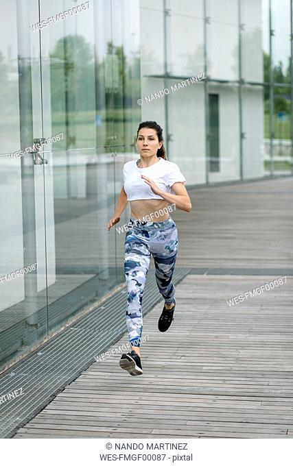 Young woman running along building in the city