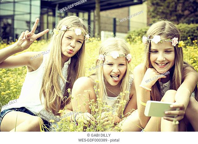 Portrait of three girls wearing floral wreaths taking a selfie on a flower meadow