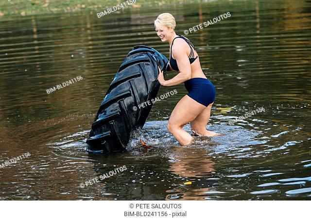 Caucasian woman pushing heavy tire in lake