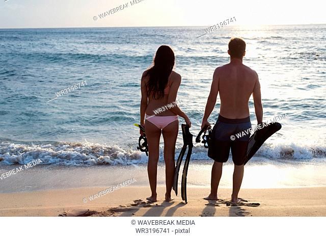 Couple standing with snorkeling equipments on the beach