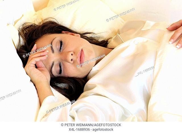 Pretty woman in pajamas sleeping in bed