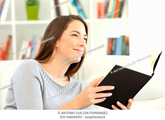 Woman dreaming reading a book and looking away sitting on a sofa at home