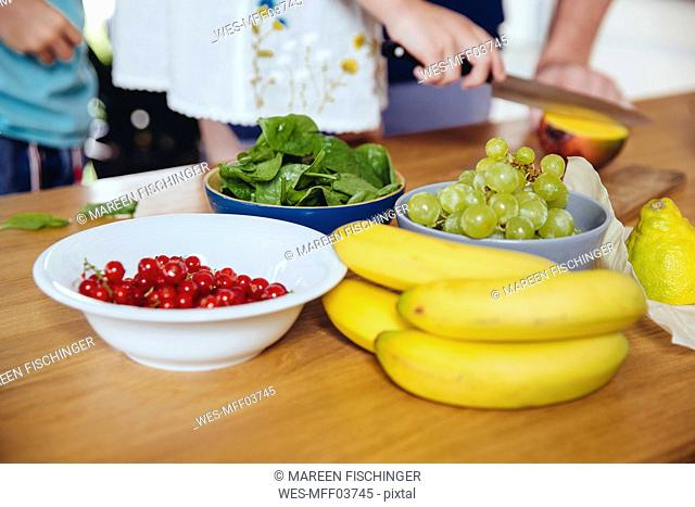 Close-up of family cutting fruit on kitchen counter