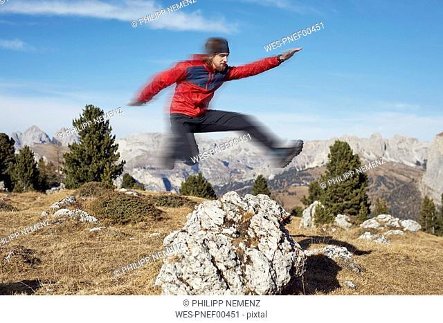 Young man jumping over rock in mountains