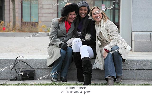 Three women friends enjoying talking in the city