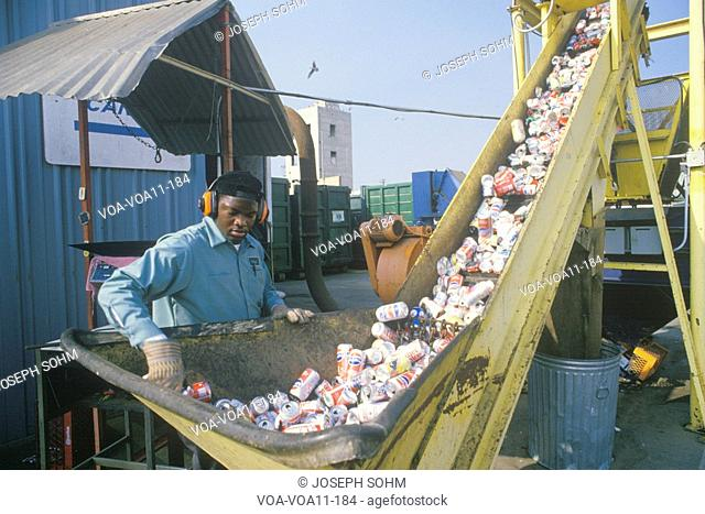 A worker overseeing aluminum cans moving along a conveyor at a recycling center in Santa Monica, CA