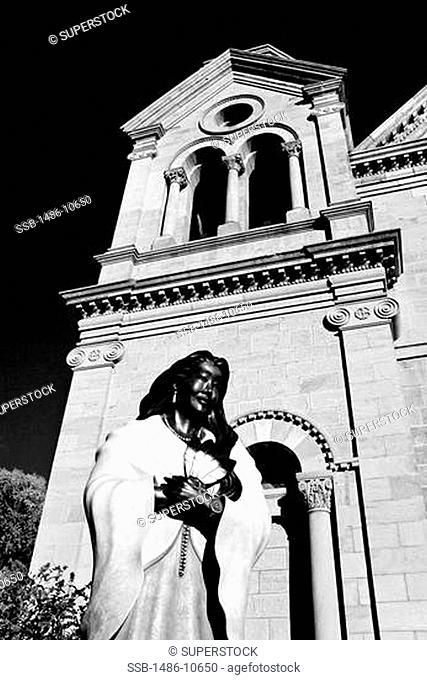 Low angle view of a statue of St. Kateri Tekakwitha in front of a cathedral, St. Francis Cathedral, Santa Fe, New Mexico, USA