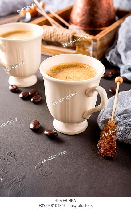 Two retro cups of coffee and old coffee pot on dark brown background with copy space
