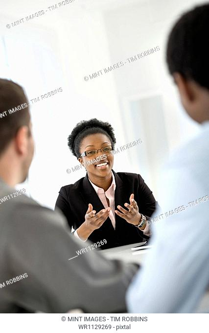 A fresh white building interior, flooded with light. Three people sitting around a table at a business meeting
