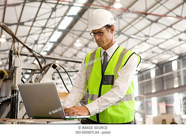 Mature man using laptop in factory