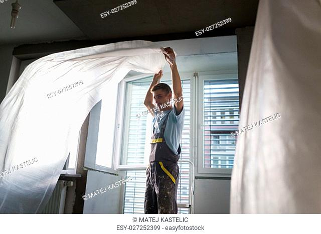 Construction worker wearing worker overall installing protective foil. House apartment renovation. Construction finishing works