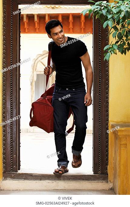 man coming through doorway with duffel bag