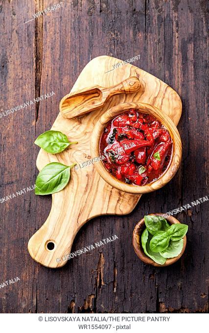 Strawberry salsa in wooden bowl on dark wooden background