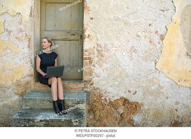 Italy, Tuscany, Monteriggioni, woman sitting at house entrance using laptop