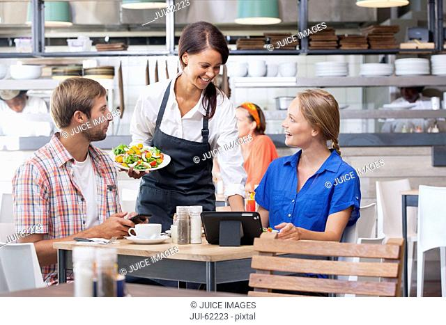 Smiling waitress serving salad plates in restaurant