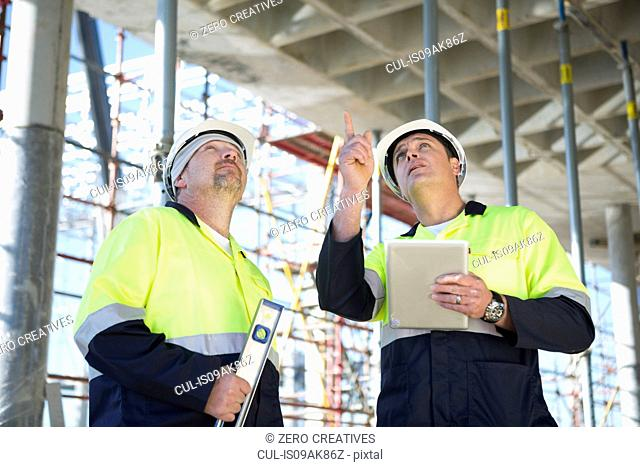 Site manager and builder looking up on construction site