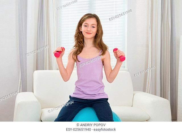 Happy Girl Holding Dumbbells While Sitting On Fitness Ball In Living Room
