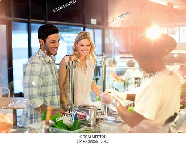 Female worker helping young couple at deli counter in grocery store market