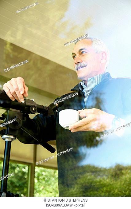 Senior man at home, drinking coffee, using telescope through window