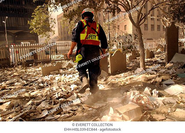 NYC firefighter walks among the old headstones at Trinity Church Cemetery in lower Manhattan. Sept. 19, 2001. The church grounds contain the graves of notable...