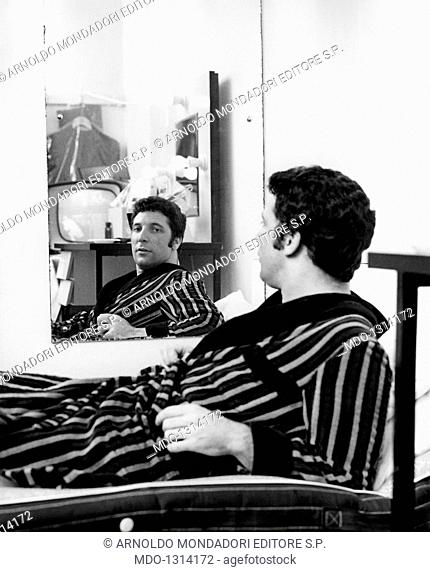Tom Jones lying down on the bed. The British singer Tom Jones (Thomas John Woodward) looking at himself in the mirror lying down on the bed