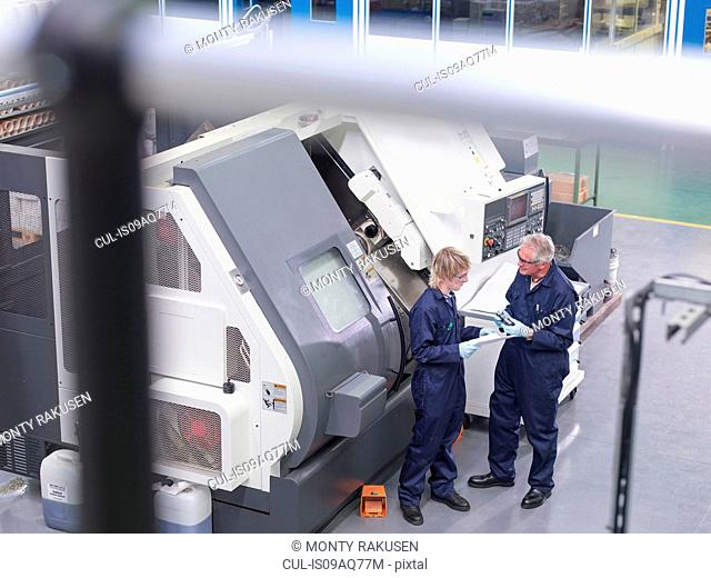 Senior engineer instructing apprentice on factory machinery, high angle view