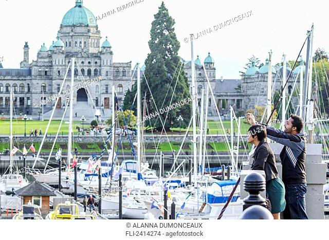 A young Indian ethnicity couple photographing Victoria Harbour; Victoria, Vancouver Island, British Columbia