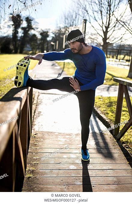 Spain, Gijon, athlete stretching in park