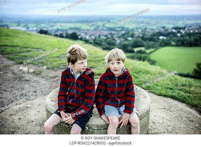 England, Somerset, Glastonbury. Two boys at the top of Glastonbury Tor at dusk