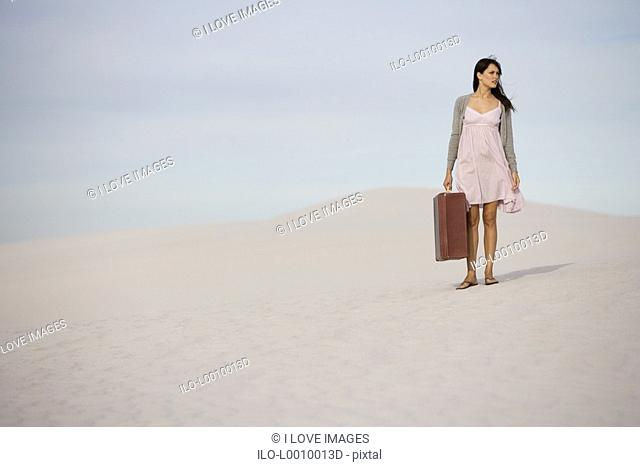 A young woman walking in the desert carrying a suitcase