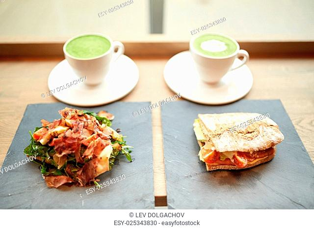 food, dinner, haute cuisine and eating concept - prosciutto ham salad with salmon panini sandwich on stone plates and cups of matcha green tea latte at...
