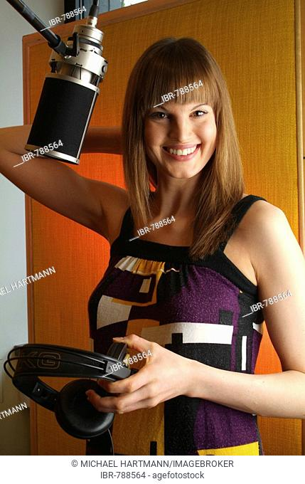 Smiling young woman holding headphones, standing next to a microphone of a recording studio