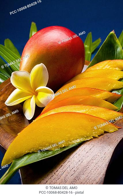 Studio shot of mango, whole and cut into slices, with flowers