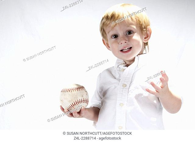 Small boy with a softball in a white button down shirt against a white background
