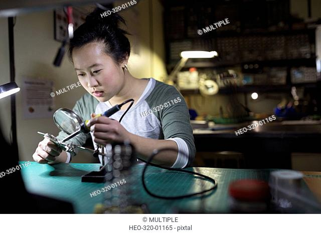 Female electronics engineer using soldering iron at workbench in workshop