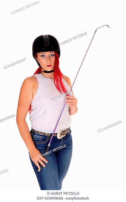 A happy woman with her rider helmet and whip, with long red hair.standing isolated for white background.