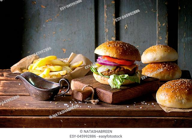 Fresh homemade burger on little cutting board with grilled potatoes, served with ketchup sauce and sea salt over wooden table with gray wooden background