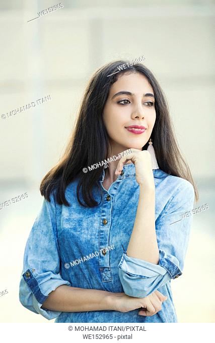 Happy young woman standing outdoors looking away
