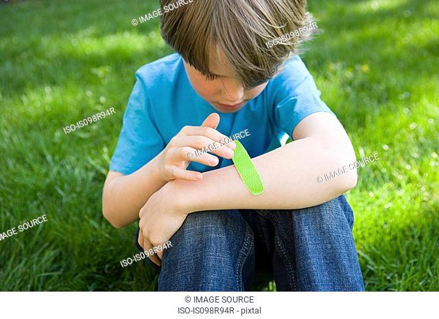 Boy putting plaster on arm