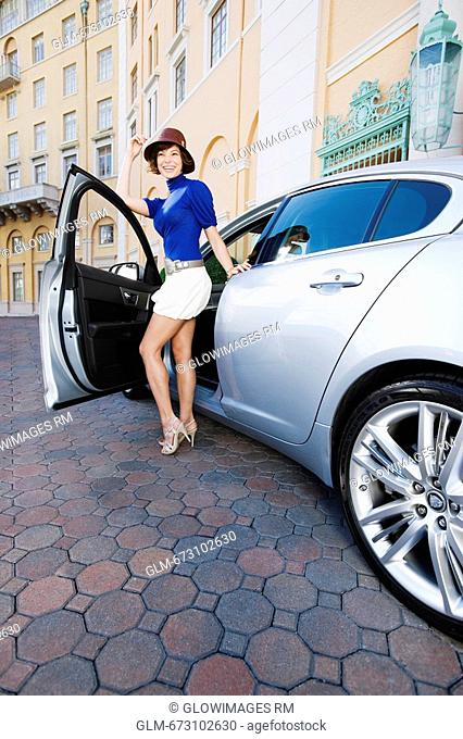 Woman getting out of a car and smiling, Biltmore Hotel, Coral Gables, Florida, USA
